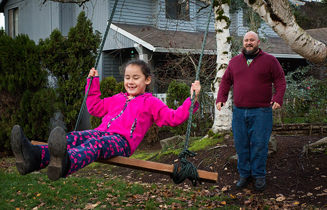 Todd Van Hess pushes his daughter on a swing that hangs from a tree in their yard.