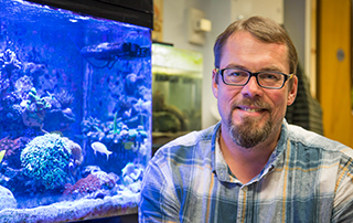 Oregon State biology instructor Andrew Bouwma sits next to a large fish tank.