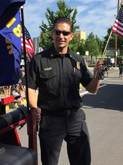 Executive Master of Public Policy student Bob Horton stands on the back of a fire truck during a parade in White City, Oregon.