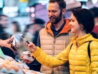 Two shoppers purchase eggs at an outdoor market, with a woman holding a smartphone as she scans a hand-held payment device