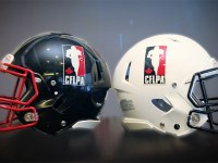 A black football helmet and a white football helmet, each bearing the logo for the Canadian Football League Players' Association, rest on a table. The CFLPA and Oregon State formed a collaboration to help professional football players earn their degrees online.
