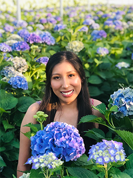OSU Ecampus student Esmeralda Sanchez stands amid a large collection of hydrangea flower bushes. She is an online fisheries and wildlife sciences student.
