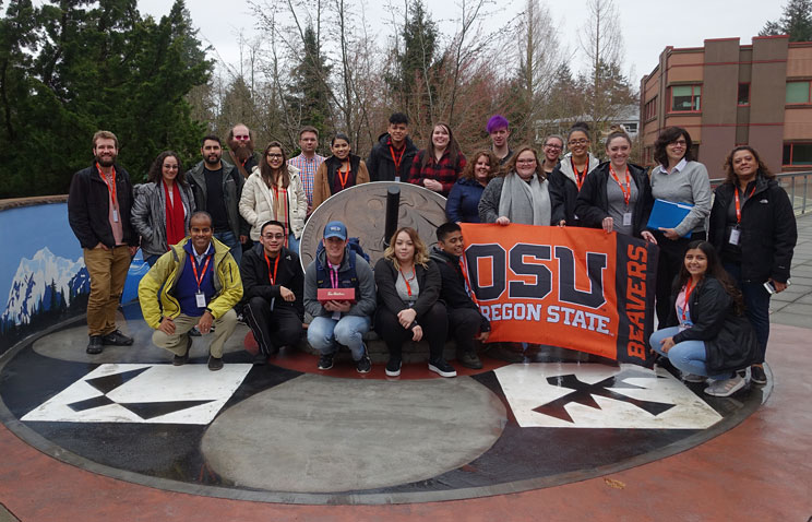 The study abroad group holds up an OSU banner at the University of the Fraser Valley, pictured with a small class of students from the university. Adrianna is seated in the center of the front row.