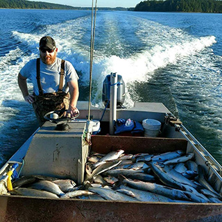 Joe Peters on a boat in a river with his catch of salmon