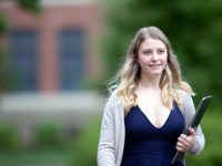 Fisheries and wildlife sciences alumna Jordan walks outdoors and carries a tablet in the bend of her left arm.