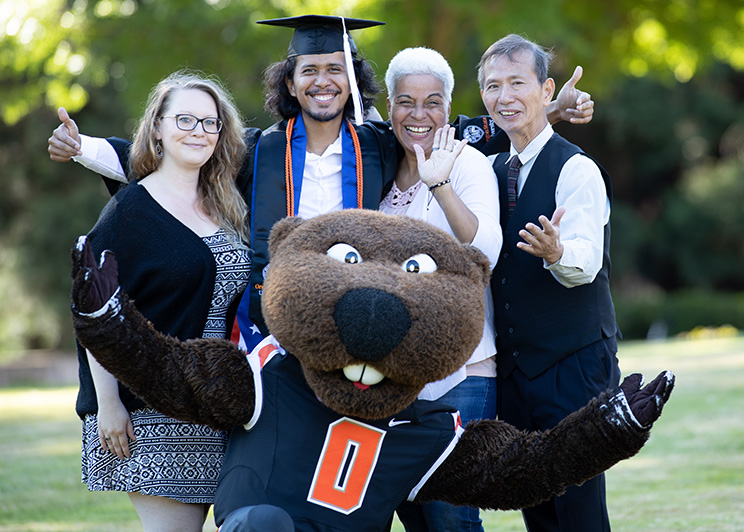Joshua Chan Burgos, an OSU Ecampus graduate, wears a graduation cap and gown while surrounded by his family and OSU's mascot, Benny the Beaver