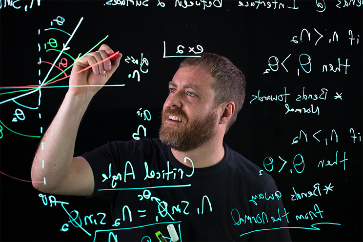 Oregon State physics instructor K.C. Walsh writes on a lightboard (a transparent whiteboard that allows the instructor to face their students as they write or draw).