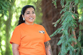Luhui Whitebear, the assistant director of Oregon State's Native American Longhouse Eena Haws, stands amid trees outside the NAL.