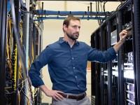 Mark Moore, Oregon State University Ecampus computer science postbaccalaureate graduate, standing in a server room.