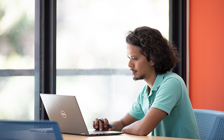 A student sits at a table while working on his laptop, a typical online learning environment