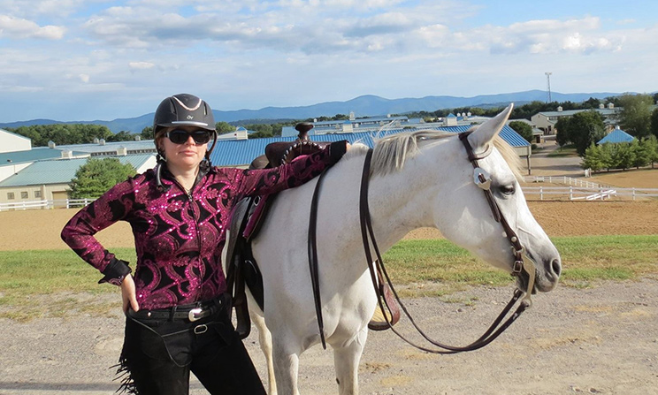 Oregon State Ecampus radiation health physics master's student Rebecca Jaronski stands next to a horse as part of a Western dressage competition
