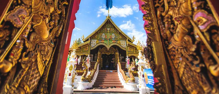 A Buddhist temple, part of the focus of Oregon State's religious studies online degree program. The temple is ornately designed with vibrant gold, red, blue, green and white statues and designs.