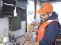 Oregon State professor Byron Crump is in the lab of the Elakha research vessel on an estuary at Yaquina Bay. He is demonstrating the use of lab tools over the sink.