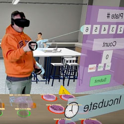 A student in an orange Oregon State hooded sweatshirt uses a virtual reality headset to complete a lab assignment. The virtual environment the student is in shows Petri dishes filled with samples on a table and lab tables in the background.