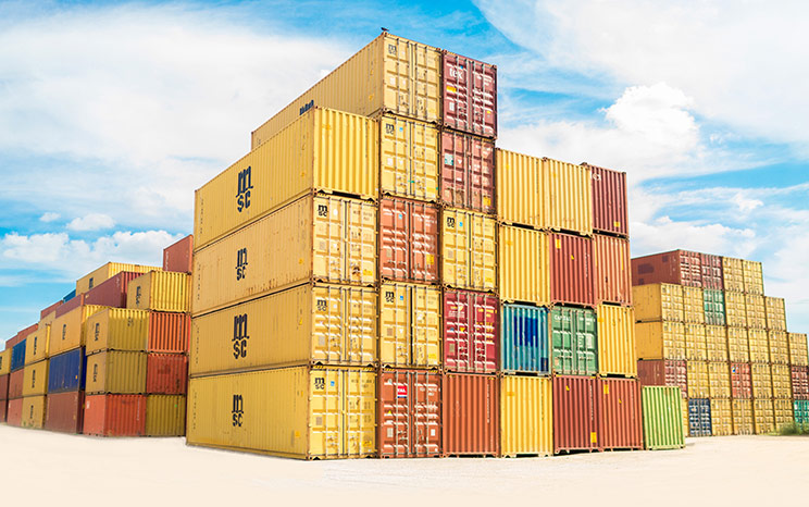A cluster of large yellow, orange, blue and green shipping containers are stacked several levels high against a bright blue, cloudy sky.