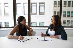 Two women during an interview smiling and taking notes.