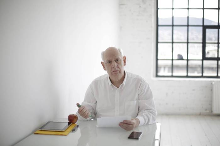 An elderly man sits a table looking confused and sad about a piece of paper he's holding. As LegalShield Associates, we will help you with finding the right service for you.