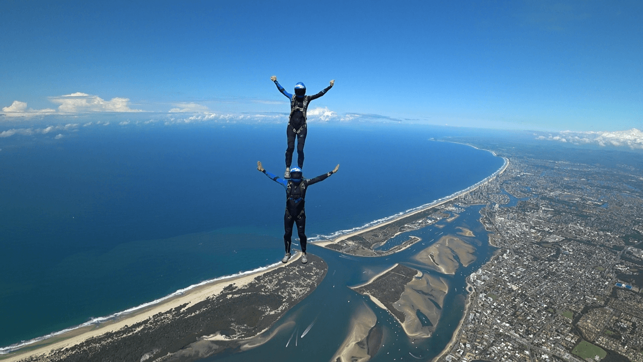 two people skydiving, with one standing on the other's shoulders
