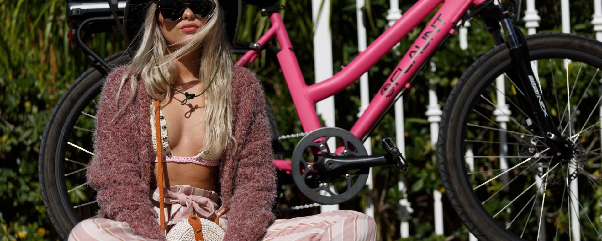 woman in bikini, sweater and black bucket hat sitting on ground in front of pink electric bicycle