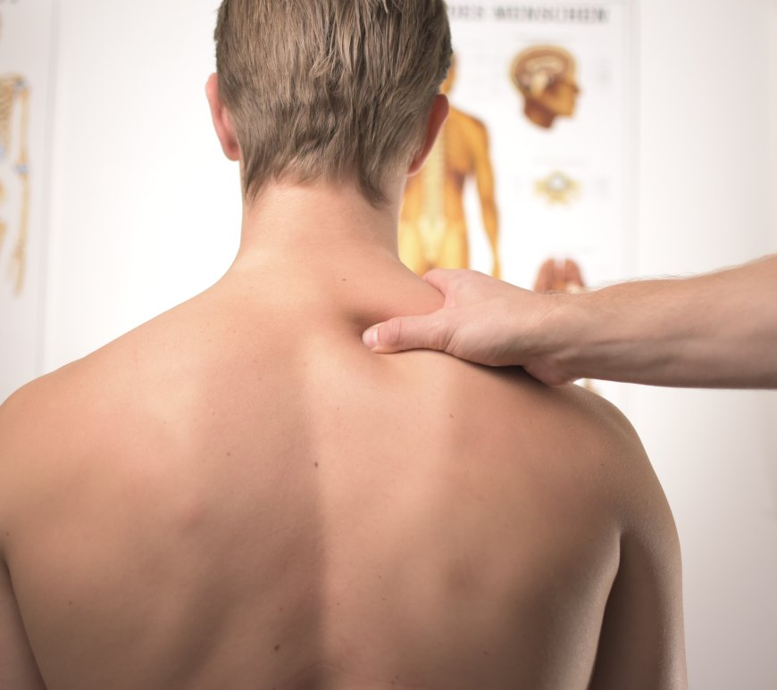 doctor touching man's bare back and neck in medical office
