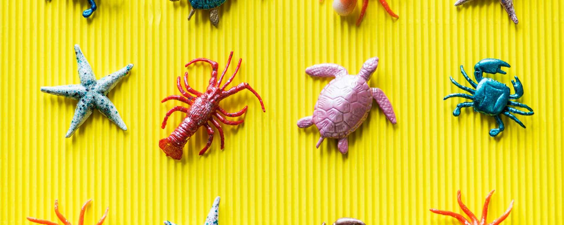 turtle and sealife plastic toys on yellow background
