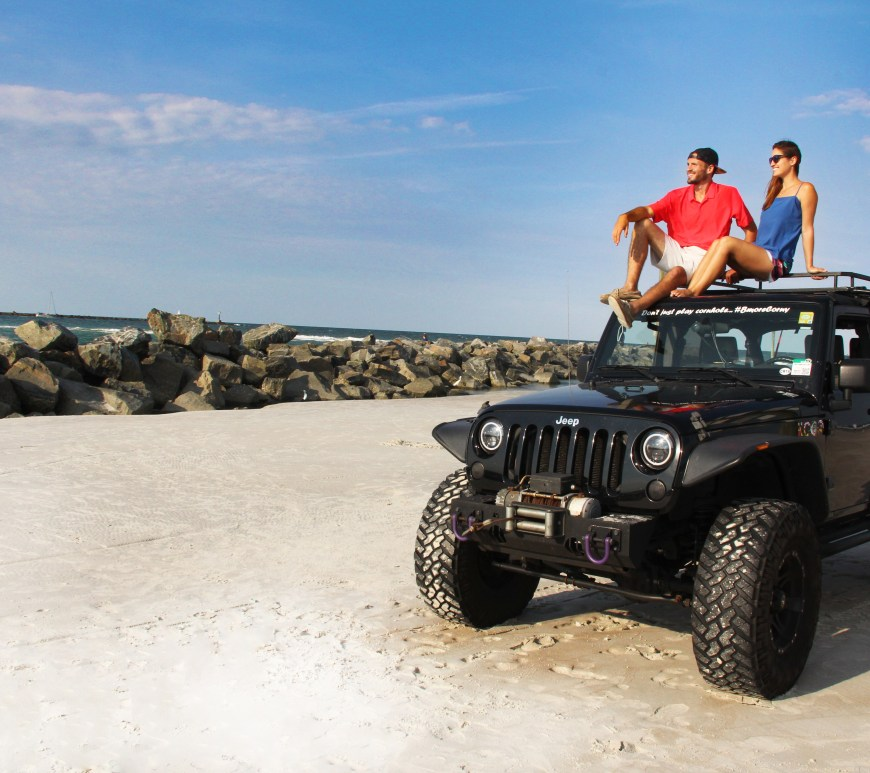 man and woman sitting on top of black jeep on sandy and rocky beach