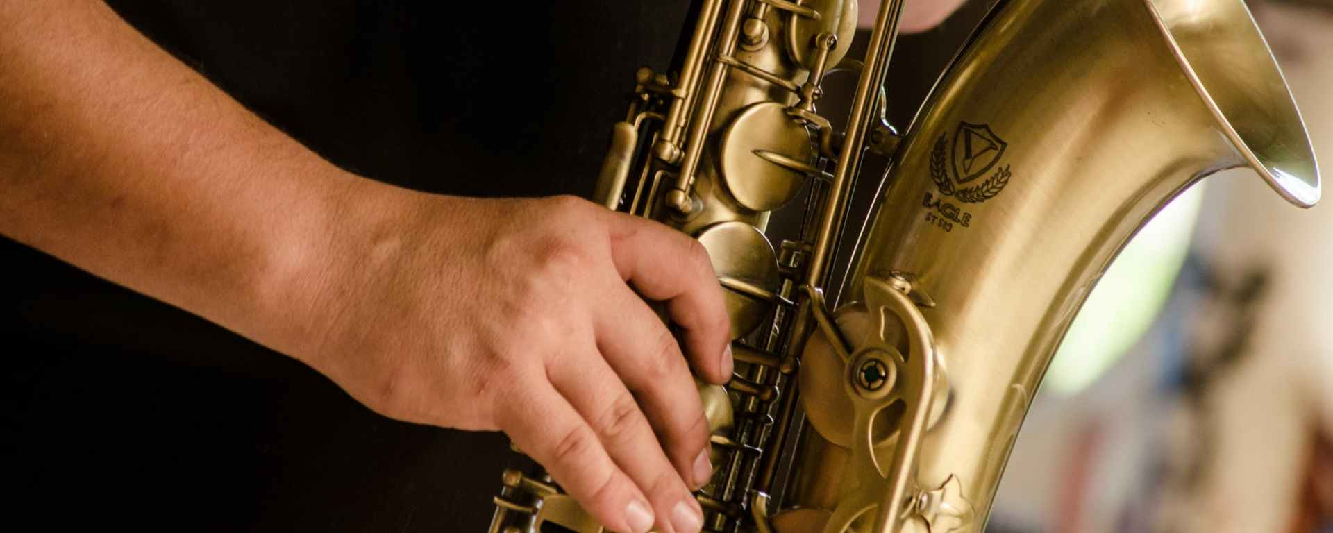 person in black shirt playing brass colored saxophone