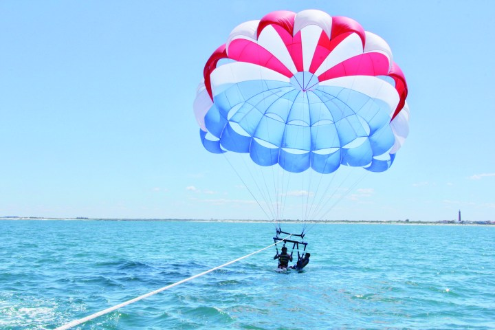 two boys parasailing while being dipped in the water