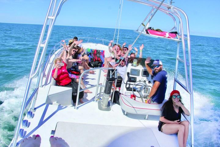 Ariel view of people on white boat in blue ocean