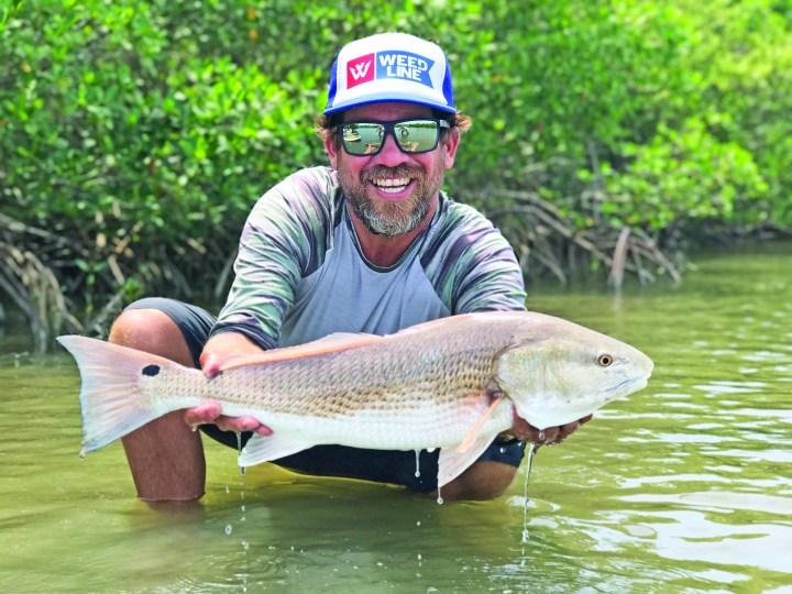 Patrick Tupat Eichstaedt fishing in backwater creek holding large fish