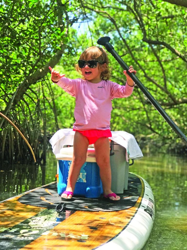 little girl fishing in backwaters on paddle board