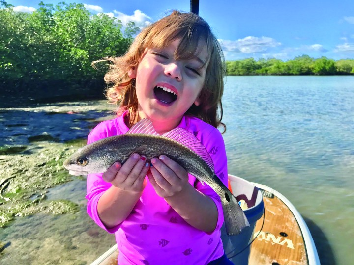 small girl in pink smiling with small fish