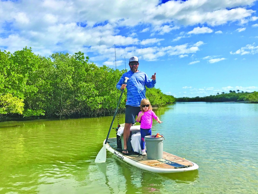man and small girl on paddle board in shallow river water