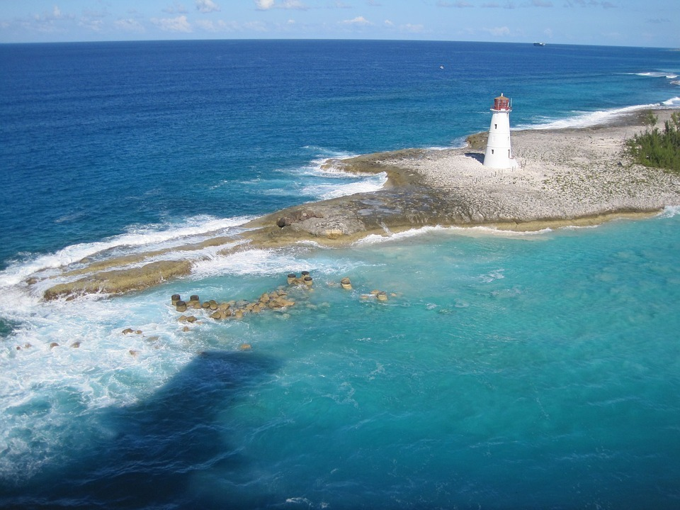 blue ocean water surrounds small lighthouse on tiny island