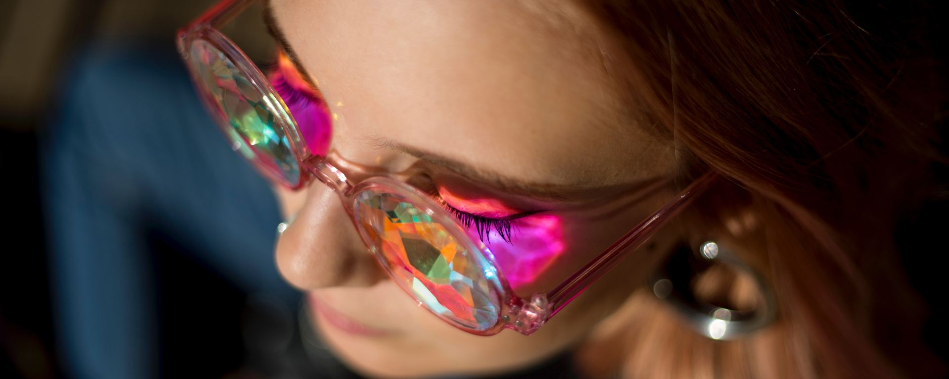woman wearing prism glasses casting pink tint on face