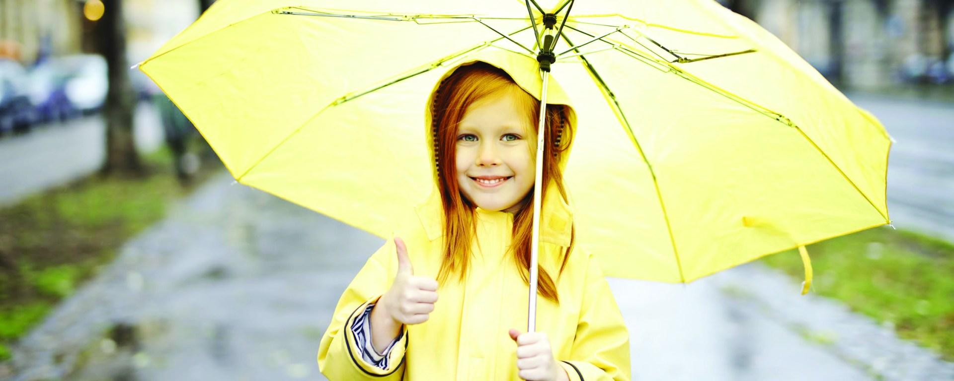 little girl in yellow rain coat under a yellow umbrella