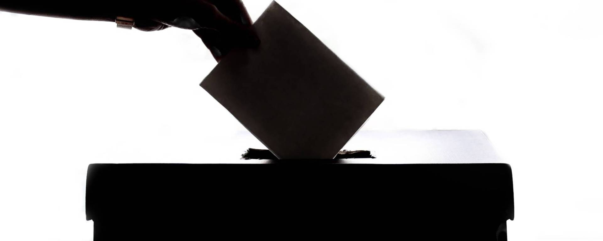 voter placing ballot in box