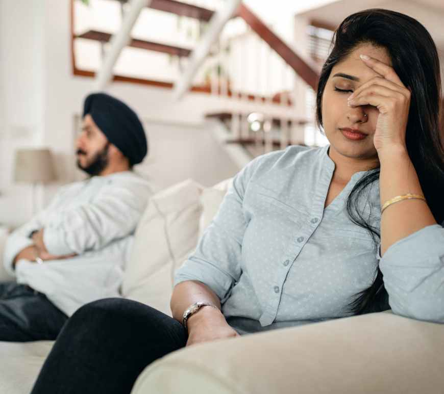 woman frustrated holding head with man next to her on couch