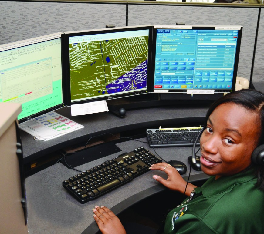volusia sheriff's office communication employee at desk with multiple screens