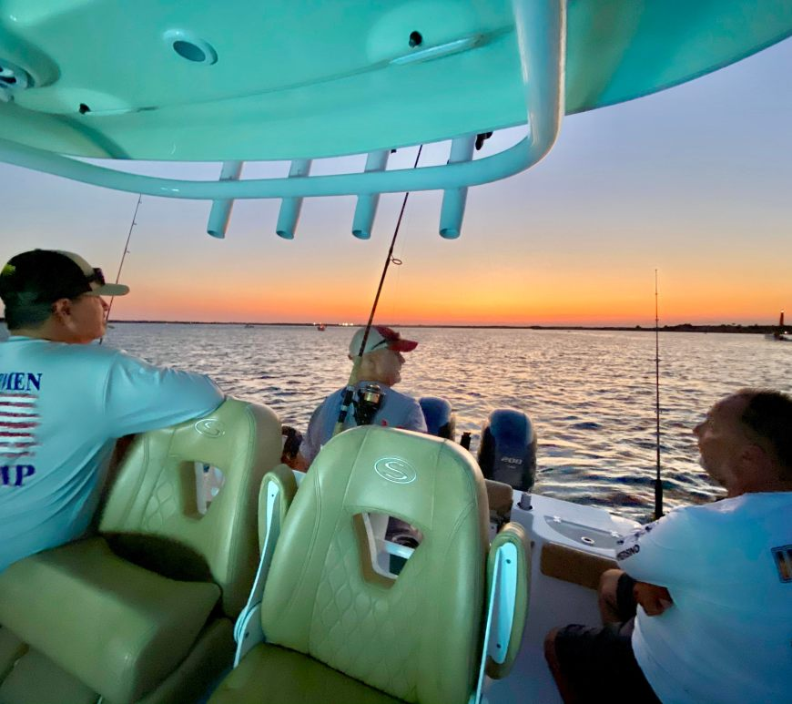 group of men sit on fishing boat looking at water at sunset