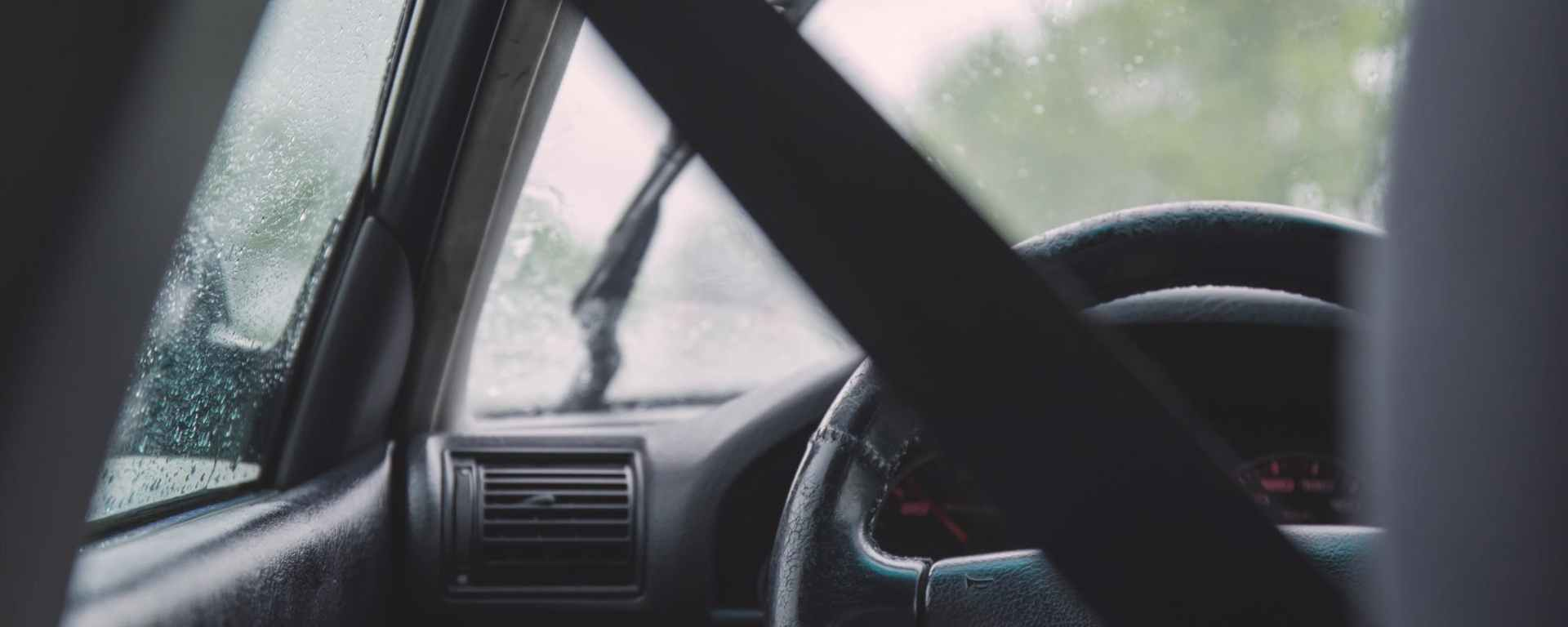 seatbelt on driver in car on rainy day