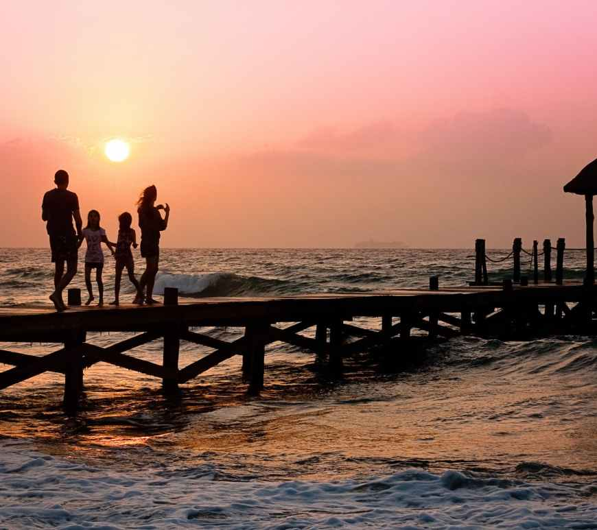 family walking on wooden pier at sunset