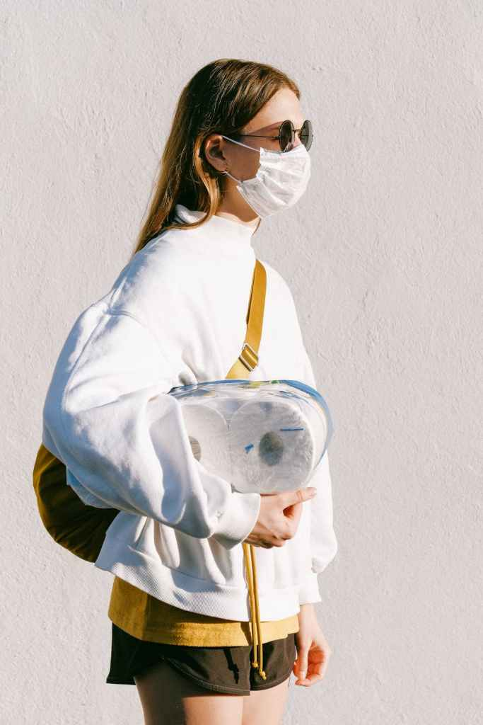 woman with bag wearing face mask