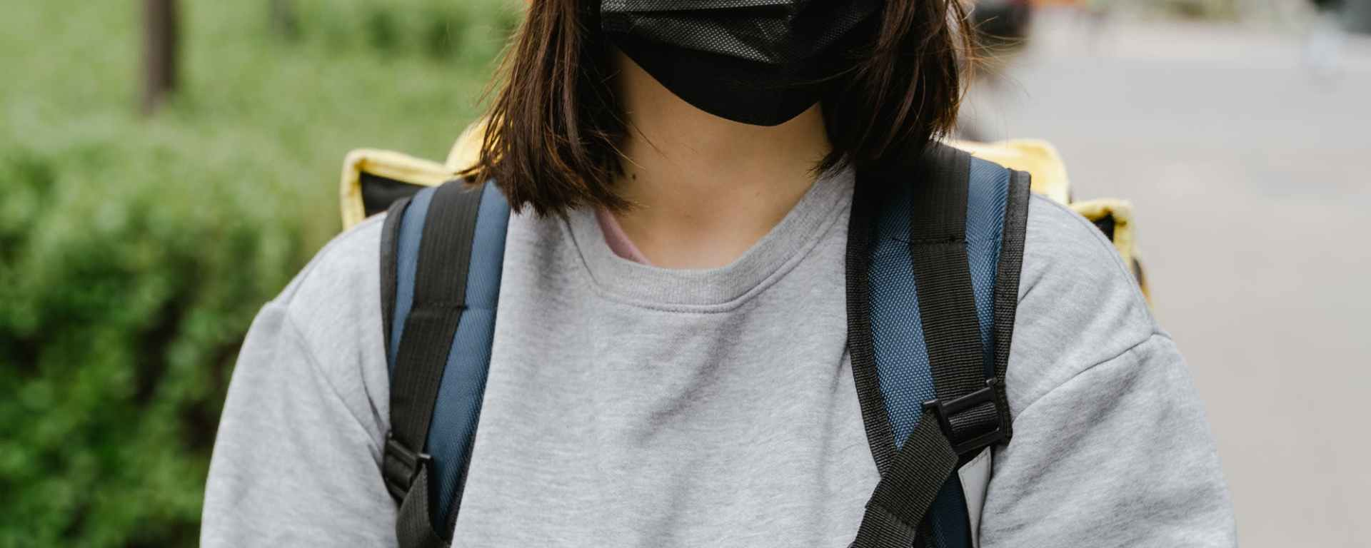 pexels-woman walking down street wearing face mask and holding phone