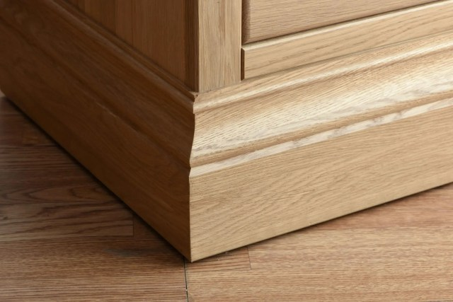 Image of Oak plinth on a oak bedside cabinet, shows the grain and quality of wood and grain. Image showing on Edmunds & Clarke Furniture Blog