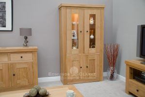 Hadleigh solid oak chunky display unit with lights. Light lacquered finish. square rustic knobs, adjustable glass shelves in the top and solid oak shelves in bottom cupboard