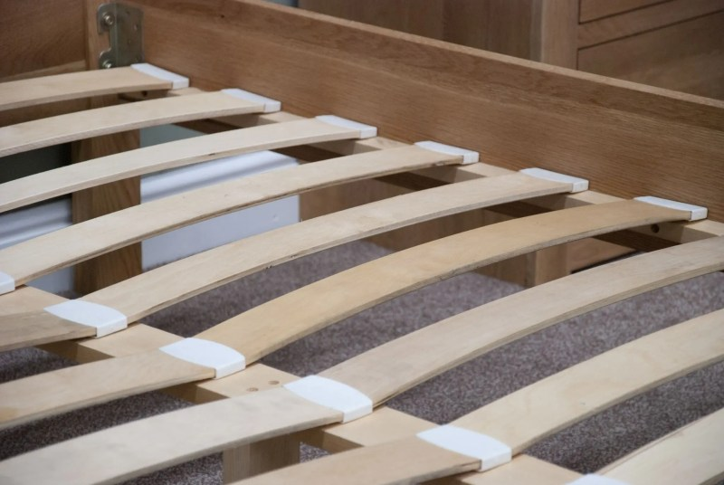 Image of typical bed slats in Edmunds & clarke Oak bed range. slats fit into cups to keep in place