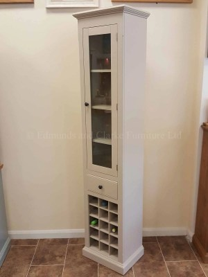 Edmunds Painted Tall Narrow Glazed Cupboard. image showing dunwich stone and premium pattern knob in pewter. wine rack under that holds 15 bottles