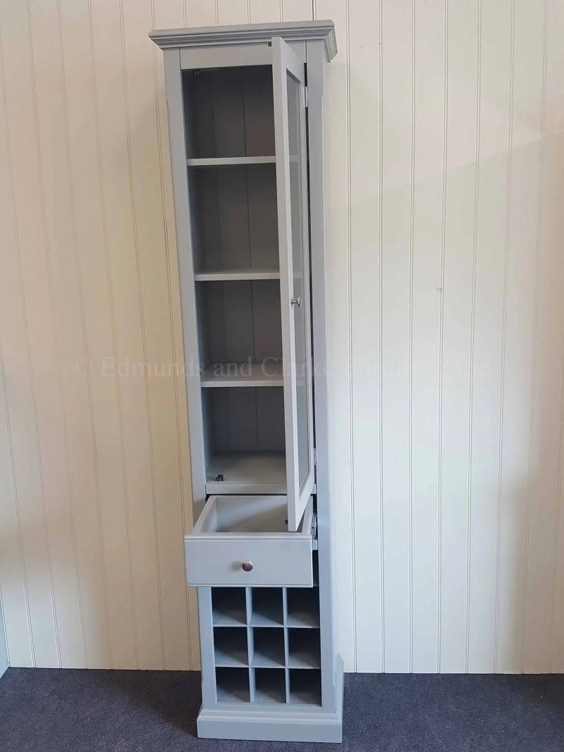 Tall narrow glazed cupboard with drawer and wine rack below