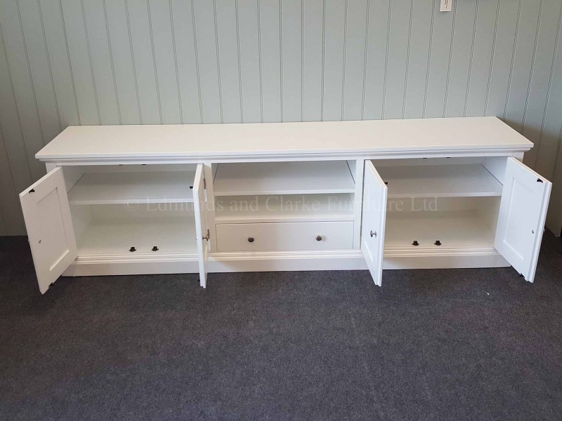 Painted white tv entertainment stand wide with cupboards and drawer and open central space